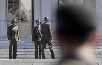FILE - Three North Korean soldiers talk each others as a South Korean soldier watches, at the border village of Panmunjom in the Demilitarized Zone between North and South Korea, April 18, 2018.