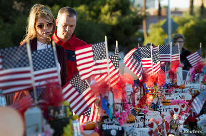 """FILE - A couple looks over 58 wooden crosses, with the names and photos of the October 1 mass shooting victims, in the median of Las Vegas Boulevard South near the """"Welcome to Las Vegas"""" sign in Las Vegas, Nevada, Oct. 9, 2017."""