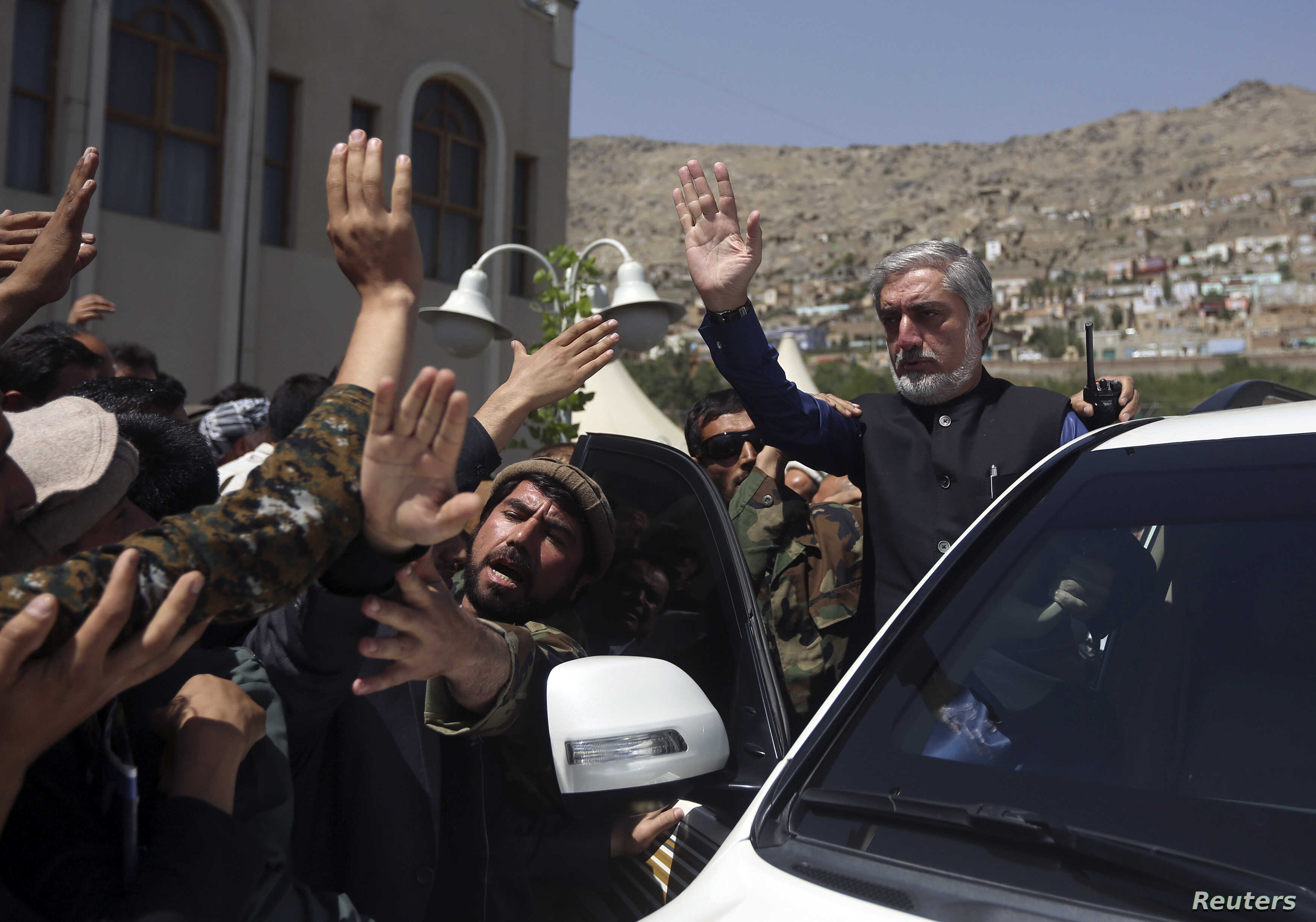 Afghan presidential candidate Abdullah Abdullah (R) waves after a ceremony commemorating the 2001 assassination of legendary Tajik resistance commander Ahmad Shah Massoud, in Kabul, Afghanistan, Sept. 9, 2014.