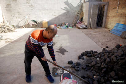 A man shovels coal he uses to heat his home in his courtyard in the village of Heqiaoxiang outside of Baoding, Hebei province, China, Dec. 5, 2017.
