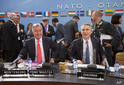 NATO Secretary General Jens Stoltenberg, right, and Montenegro's Prime Minister Milo Dukanovic, left, take their seats during a meeting of the North Atlantic Council and Montenegro at NATO headquarters in Brussels, May 19, 2016.