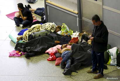 Migrants sleep in the hall of main railway station in Munich, Germany, Sept. 13, 2015.