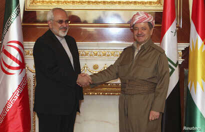 Iraqi Kurdish regional President Masoud Barzani, right, shakes hands with Iranian foreign minister Mohammad Javad Zarif in Arbil, north of Baghdad, Aug. 26, 2014.