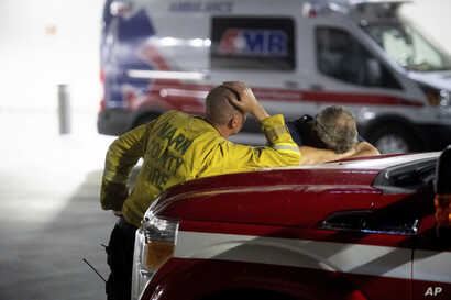 Marin County firefighters wait outside the Mercy Medical Center emergency room as an injured crew member receives treatment on July 26, 2018, in Redding, Calif.