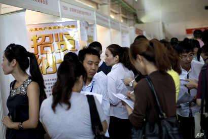 FILE - Chinese job seekers visit a job fair held at the China International Exhibition Center in Beijing.