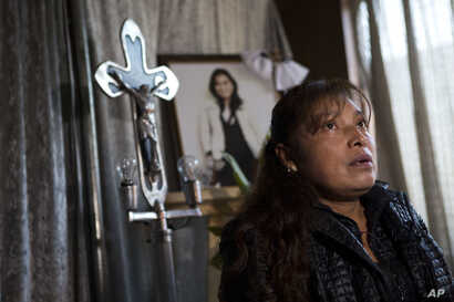 Juana Pedraza sits by a shrine to her slain daughter Jessica Sevilla Pedraza, a 29-year-old doctor and mother, during an interview inside her family's home in Villa Cuauhtemoc, Mexico state, Aug. 18, 2017.