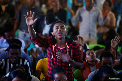 A man attends a prayer session at Biftu Bole Lutheran Church during a prayer and candle ceremony for protesters who died in the town of Bishoftu two weeks ago during Irreecha, the thanksgiving festival of the Oromo people, in Addis Ababa, Ethiopia, O...
