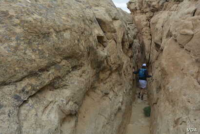 National parks traveler Mikah Meyer navigates his way through naturally-formed passageways that lead to a stone shelf overlooking the ancient structures at Chaco Culture National Historical Park.