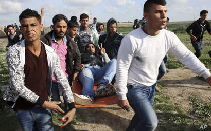 Palestinian protesters evacuate a wounded person during clashes with Israeli troops on the Israeli border with Gaza, east of Gaza City, March 16, 2018.