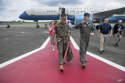 Joint Chiefs Chairman Gen. Joseph Dunford is welcomed by Lt. Gen. Jerry Martinez, center right, as he arrives at Air Base in Fussa, Japan, Aug. 13, 2017, for a refueling stop.
