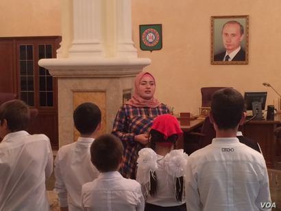 """One should wait for a while to make comments on history,"" says Luiza Khatueva, a tour guide at the Akhmad Kadyrov Museum, seen here before a group of school children, with a portrait of President Vladimir Putin in the background."
