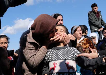 Dilbar Ali Ravu, 10, is kissed by his aunt Dalal Ravu after Yazidi children were reunited with their families in Iraq after five years of captivity with the Islamic State group, March 2, 2019.