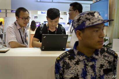FILE - Visitors use a laptop computer at a display booth as a security guard stands nearby at the Global Mobile Internet Conference in Beijing, April 29, 2015.