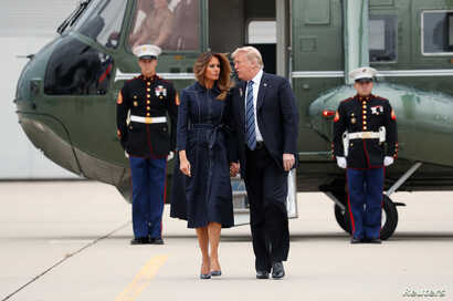 FILE - U.S. President Donald Trump and first lady Melania Trump hold hands and talk as they walk from the Marine One helicopter to Air Force One at John Murtha Johnstown-Cambria County Airport  prior to departing Johnstown, Pennsylvania, Sept. 11, 20...