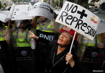 """An opposition supporter confronts riot security forces with a sign that reads """"No more repression"""" during a rally against President Nicolas Maduro in Caracas, Venezuela, May 12, 2017."""