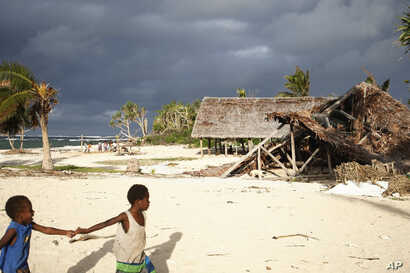 FILE - Children play on the beach in the town of Takara, on Efate Island, Vanuatu, May 30, 2015. The town was damaged in March of that year during Cyclone Pam. Many people in the town considered rebuilding on higher ground to escape what they thought