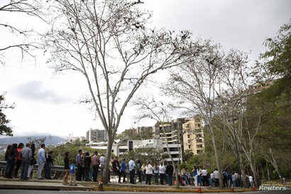 People, many of whom are seeking visas, form a line outside the U.S. Embassy in Caracas, March 4, 2015.