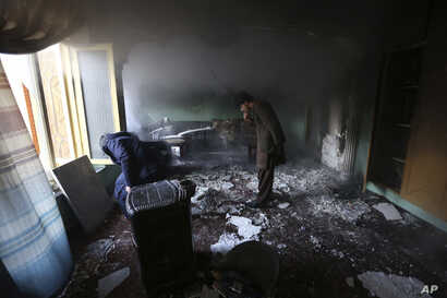 Afghan men inspect the remains of their belongings at the house of parliament member Mir Wali in the aftermath of gunmen's attack late Wednesday in western Kabul, Afghanistan, Dec. 22, 2016.