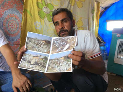 At a refugee camp near Mosul, Ibrahim Makhool holds up pictures of his house that was destroyed in an airstrike against Islamic State militants in December, killing two of his three children, in Hammam Alil, Iraq, June 21, 2017.