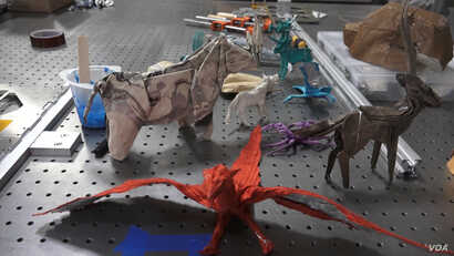 Examples of creatures folded out of paper by Robert Salazar are spread out on a workbench in this image taken from video. (E. Lee/VOA)