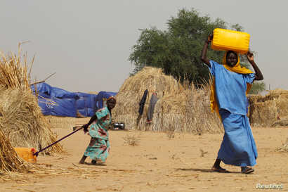 Nigerien displaced people carry water in a camp of the city of Diffa, Niger, June 18, 2016.