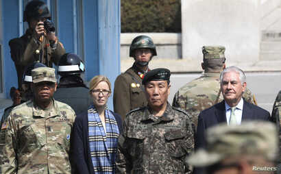 U.S. Secretary of State Rex Tillerson stands with his Chief of Staff Margaret Peterlin and deputy Commander of the Combined Force Command General Leem Ho-young (second right) as two North Korean soldiers look at the south side in the border village o...