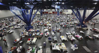 Evacuees escaping the floodwaters from Tropical Storm Harvey rest at the George R. Brown Convention Center that has been set up as a shelter in Houston, Texas, Aug. 29, 2017.