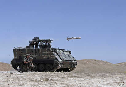 FILE - A Lebanese army vehicle fires a TOW-II missile in the village of Taybeh, near Baalbek, eastern Lebanon.