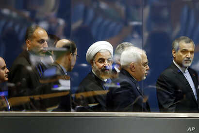 President Hassan Rouhani of Iran, center, walks with Iranian Foreign Minister Mohammad Javad Zarif, second right, as he leaves after addressing the 69th session of the United Nations General Assembly at U.N. headquarters, Thursday, Sept. 25, 2014. (A...
