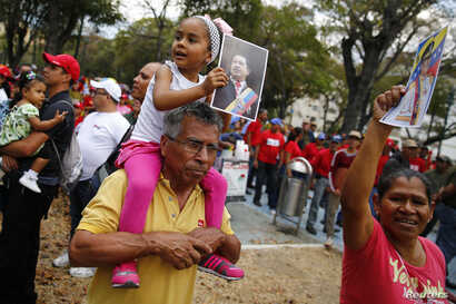 A girls taking part in a demonstration supporting Venezuela's President Nicolas Maduro's holds a picture of late president Hugo Chavez during a rally with Bolivarian militia in Caracas March 15, 2014.  REUTERS/Jorge Silva