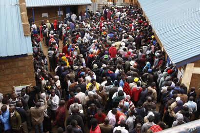 Voters line up early morning in cold weather at a polling station in the Kibera Slums in Nairobi, Kenya, Aug. 8, 2017.