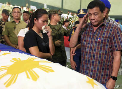 FILE -  Philippine President Rodrigo Duterte salutes flag-draped coffins of 15 soldiers killed in Monday's gun battle with Muslim Abu Sayyaf militants during his visit to Western Mindanao Command in Zamboanga city, in southern Philippines.
