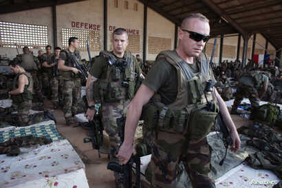 FILE - French soldiers leave a hangar at the Malian army air base in Bamako, Jan. 14, 2013. France had poured  hundreds of troops into Bamako at the time, carrying out air raids in a vast desert area seized the year before by an Islamist alliance gro...