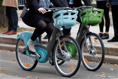 Riders present the new Velib' Metropole self-service public bicycles by the Smovengo consortium during a media presentation in Paris, France, Oct. 25, 2017.