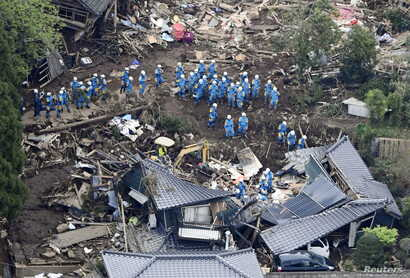 Rescue workers conduct a search and rescue operation to a collapsed house at a landslide site caused by earthquakes in Minamiaso town, Kumamoto prefecture, southern Japan, in this photo taken by Kyodo, April 16, 2016.