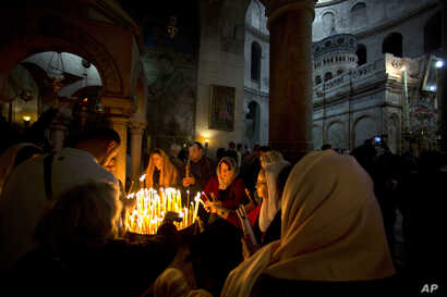 Christian pilgrims light candles during the Easter Sunday procession at the Church of the Holy Sepulchre, traditionally believed by many Christians to be the site of the crucifixion and burial of Jesus Christ, in Jerusalem, April 16, 2017.