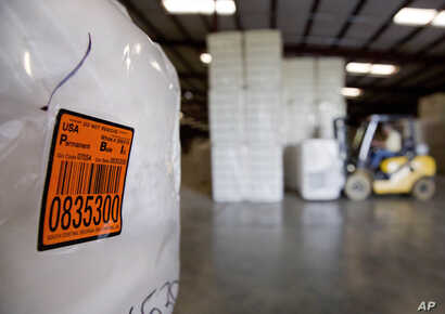 FILE - A bale of cotton sits packed and labeled while waiting to be shipped from the South Central Georgia Gin Company in Enigma, Ga., June 21, 2018. The company estimates that 40 to 50 percent of the cotton processed at the gin is exported out of th...