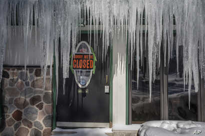 Icicles hang in front of a door at a bar in Mequon, Wis, Jan. 30, 2019 as temperatures were subzero and wind chills were at -50 degrees F.