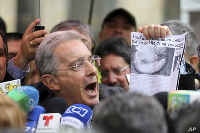 "Former President and opposition Senator Alvaro Uribe shows a clip of a news article with a headline reading in Spanish ""FARC puts a C4 collar around the neck of a Venezuelan,"" after voting in a referendum to decide whether or not to support a peace d..."