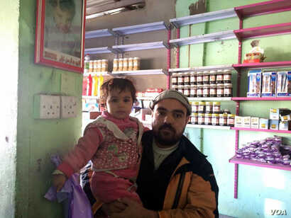 Othman Taha keeps a picture of his son, Abdulrahman hanging in his small grocery.  He says Abdulrahman was murdered under IS rule when he was 3 years old.