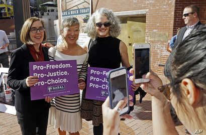 Oregon Gov. Kate Brown, left, poses for photos with supporters after a rally in Portland, Ore., Oct. 17, 2018. A measure to ban the use of state funds to pay for abortions is on the ballot in Oregon, the state with the least restrictive abortion law...