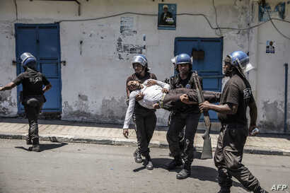 FILE- Comoros Gendarmerie officers carry an injured policeman wearing civilian clothes as they disperse opposition supporters, in Moroni, on March 25, 2019.