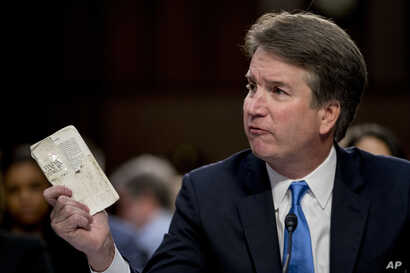 Supreme Court nominee Brett Kavanaugh, a federal appeals court judge, holds up a worn copy of the Constitution of the United States as he testifies before the Senate Judiciary Committee on Capitol Hill in Washington, Sept. 5, 2018.