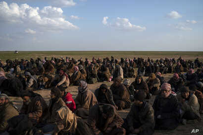 Men wait to be screened by U.S.-backed Syrian Democratic Forces fighters after being evacuated out of the last territory held by Islamic State militants, near Baghuz, eastern Syria, Feb. 22, 2019.