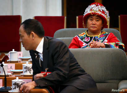 A delegate wearing a traditional costume sits down before the start of a meeting held on the sidelines of the 18th National Congress of the Communist Party of China at the Great Hall of the People in Beijing, November 8, 2012.