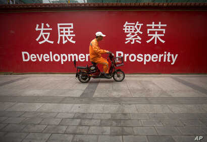 "FILE - A maintenance worker rides a scooter past banners reading ""Development"" and ""Prosperity"" in English and Chinese on a street in central Beijing, July 15, 2015."