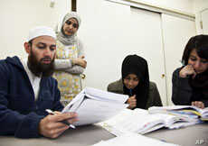 Students (from left to right) Waqas Ahmed, Sifat Reazi and Armaan Siddiqi consult with teacher Souhad Zendah (standing).