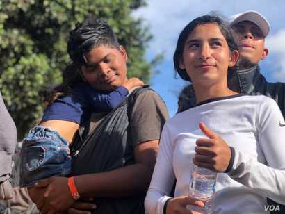 A Honduran family traveling with the caravan joined the group as they approached the pedestrian crossing with their child. Celia Mendoza/VOA