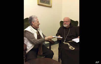 FILE - This Feb. 3, 2018 photo shows Marie Collins, a member of the Pope Francis' sex-abuse commission, hands a letter to Cardinal Sean O'Malley detailing the abuse of Juan Carlos Cruz and a cover-up by Chilean church authorities, at the Domus Santa ...