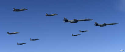 In this photo provided by South Korea Defense Ministry, U.S. Air Force B-1B bombers, F-35B stealth fighter jets and South Korean F-15K fighter jets fly over the Korean Peninsula during a joint drills, South Korea, Sept. 18, 2017.